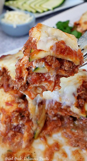 A close up photo of a bite of zucchini lasagna on a fork being held above a serving of lasagna.