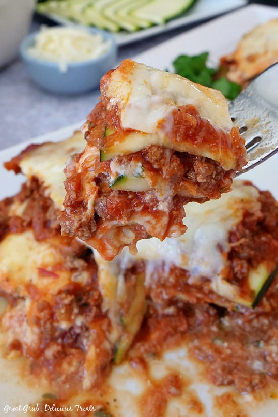 A bite of zucchini lasagna on a fork being held above a plate of lasagna.