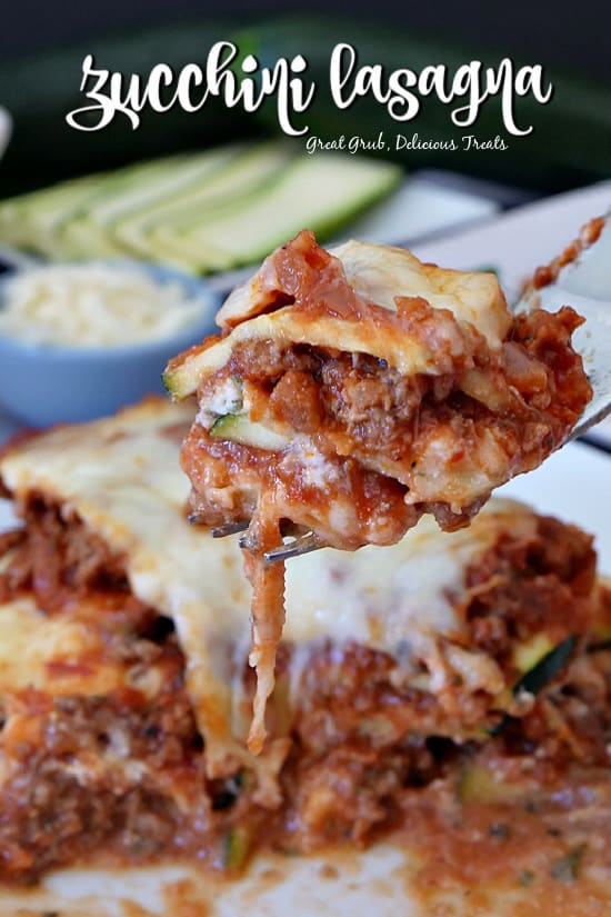 A bite of zucchini lasagna on a fork held above the plate of lasagna below with sliced zucchini and shredded cheese in the background.