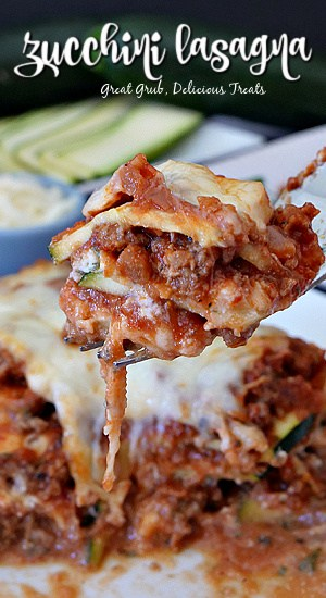 A bite of zucchini lasagna being held up over a plate of lasagna.