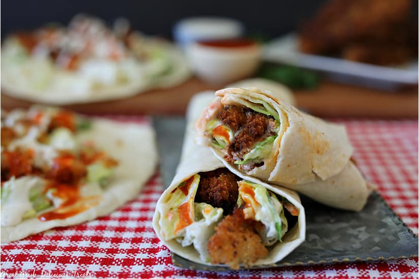 Two buffalo chicken wraps on a silver plate wrapped up showing the chicken, lettuce, and ranch dressing and buffalo wing sauce, all on a red and white checkered placemat.