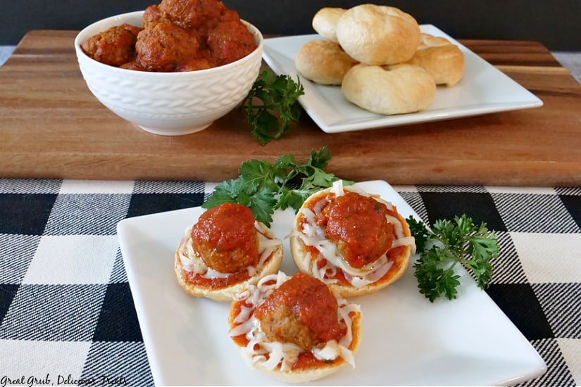 A picture of Meatball Bagel Bites on a white plate with parsley, cooked meatballs in a white bowl, and plain bagels on a white plate in the background on a brown cutting board.