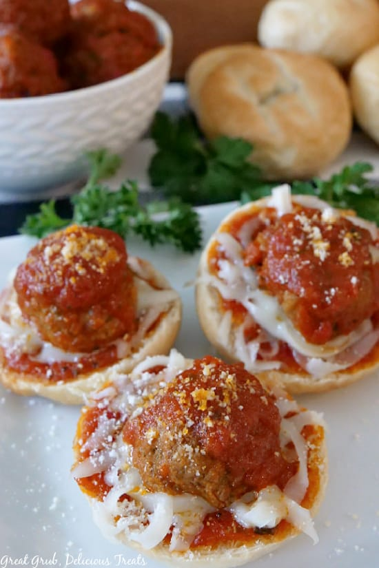 Meatball Bagel Bites on a white plate with parsley, meatballs in a white bowl, and plain bagels in the background.