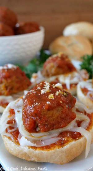 A close up picture of a Meatball Bagel Bite on a white plate with bagel bites in the background, along with parsley, cooked meatballs covered in spaghetti sauce in a white bowl, and plain bagels.