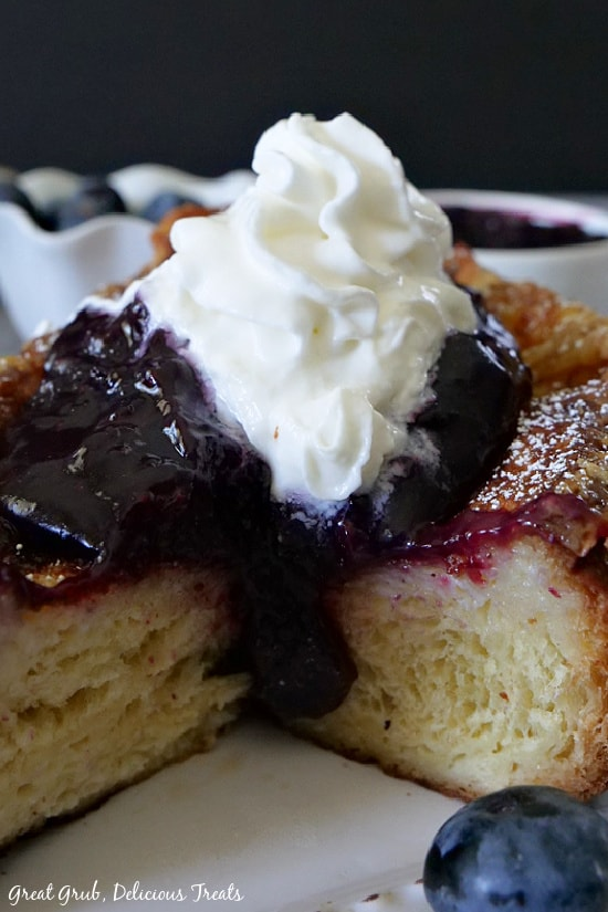 A close up photo of a slice of French Toast with Blueberry Topping on a white plate.