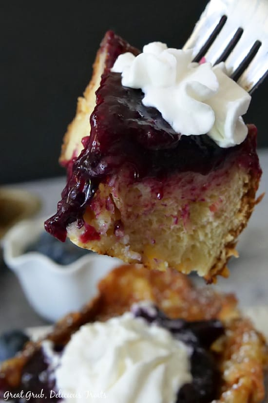 A close up photo of a bite of French Toast with Blueberry Topping on a fork.