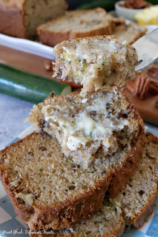 Zucchini Bread slices stacked on a blue and white checkered plate with the zucchini loaf in the background.