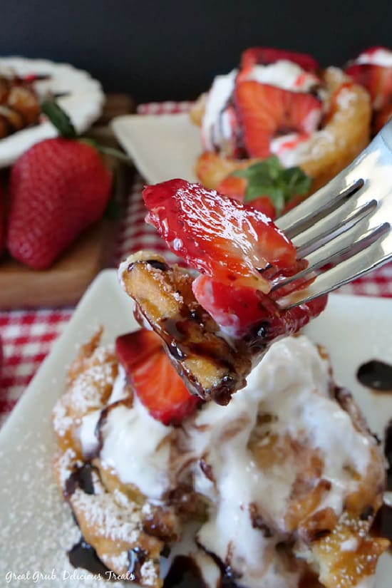 A close up picture of Strawberry Funnel Cakes on a white plate with a fork holding a bite showcasing a fresh strawberry slice and a piece of funnel cake drizzled in chocolate syrup.
