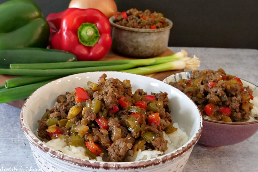 A grey and a purple bowl filled with beef and peppers over a bed of rice with green onions, red and green bell peppers and another bowl of beef and peppers rice bowl in the background.