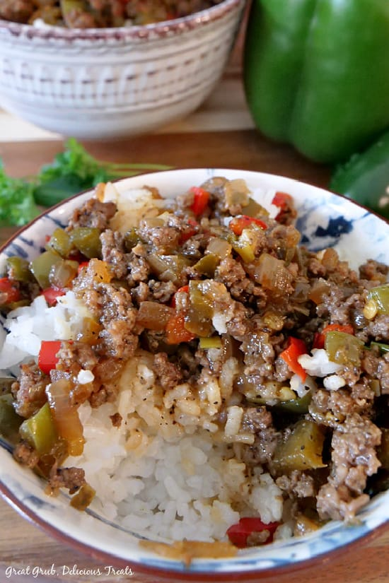 A white bowl filled with beef and peppers with a grey bowl and green bell peppers in the background.