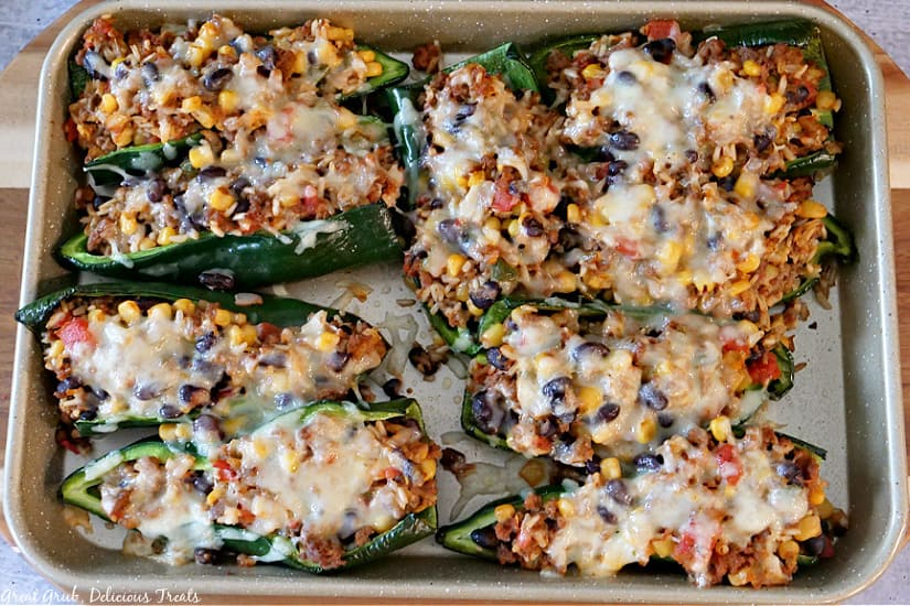 A baking sheet with stuffed poblano peppers lined up on it.