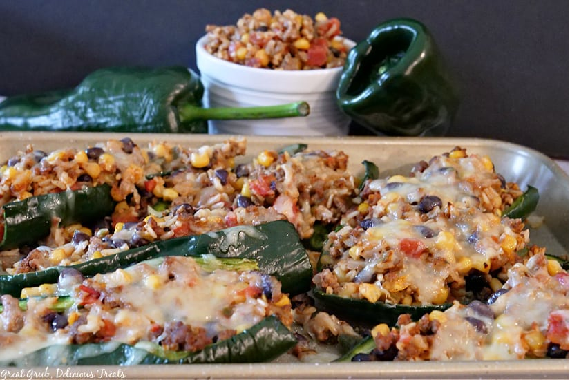 A baking sheet with stuffed poblano peppers on it.