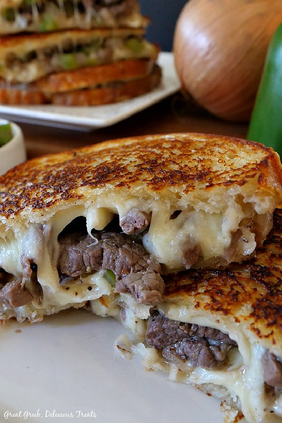 Philly Cheesesteak Grilled Cheese - two halves of this sandwich showing the cheese, meat and peppers and onions between two slices of grilled bread.