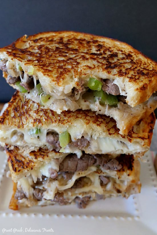 Philly Cheesesteak Grilled Cheese - four half sandwiches stacked on top of each other with a bite being taken out of one of the halves, all placed on a white plate.