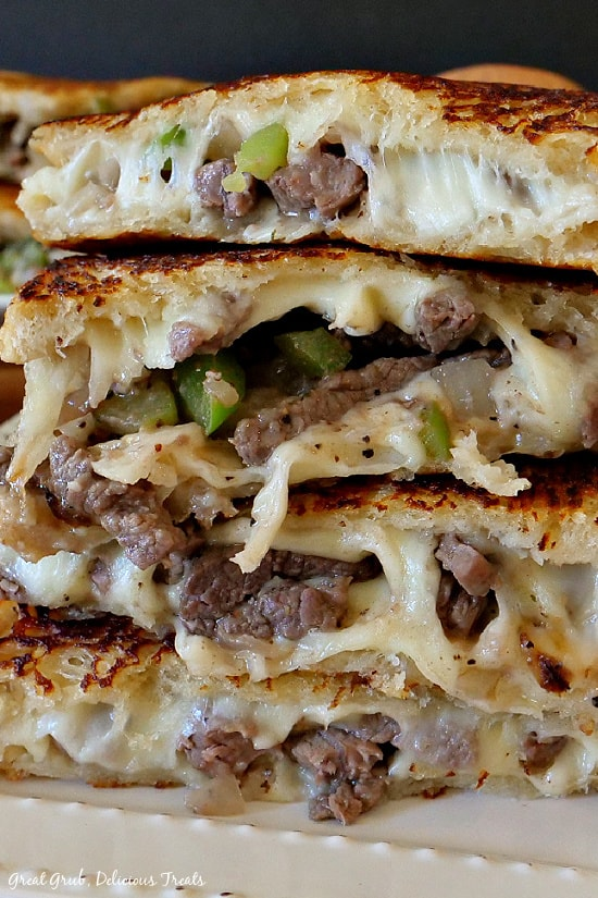A stack of Philly Cheesesteak Grilled Cheese halves stacked up on a white plate.