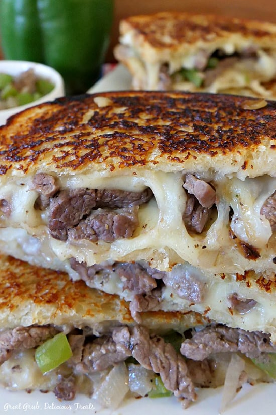 A close up photo of a Philly Cheesesteak Grilled Cheese cut in half and placed on top of each other, then placed on a white plate with another sandwich in the background.