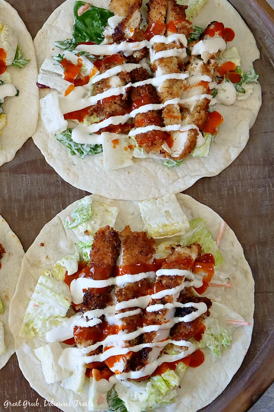 Two Buffalo Ranch Chicken Wraps on a wooden round serving tray before they are rolled up showing the crispy chicken, lettuce and drizzled with Ranch and buffalo wing sauce.