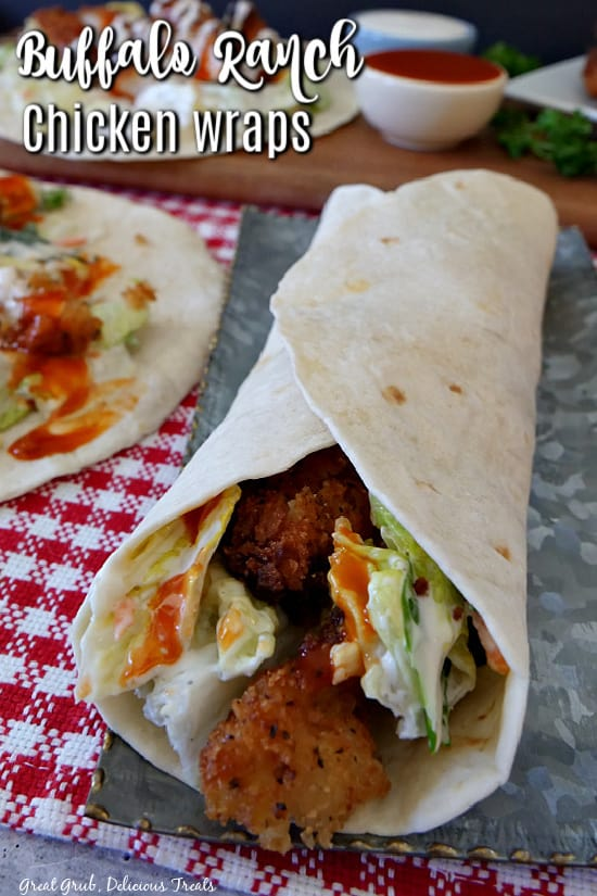 A flour tortilla filled with crispy chicken strips with lettuce and buffalo ranch dressing on a silver plate that is placed on a red and white checkered placemat.
