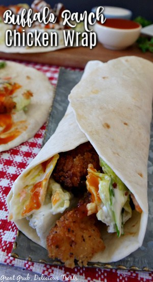 A close up photo of a flour tortilla wrapped around crispy chicken strips, with lettuce, ranch and buffalo sauce on a silver plate placed on a red and white checkered placemat.