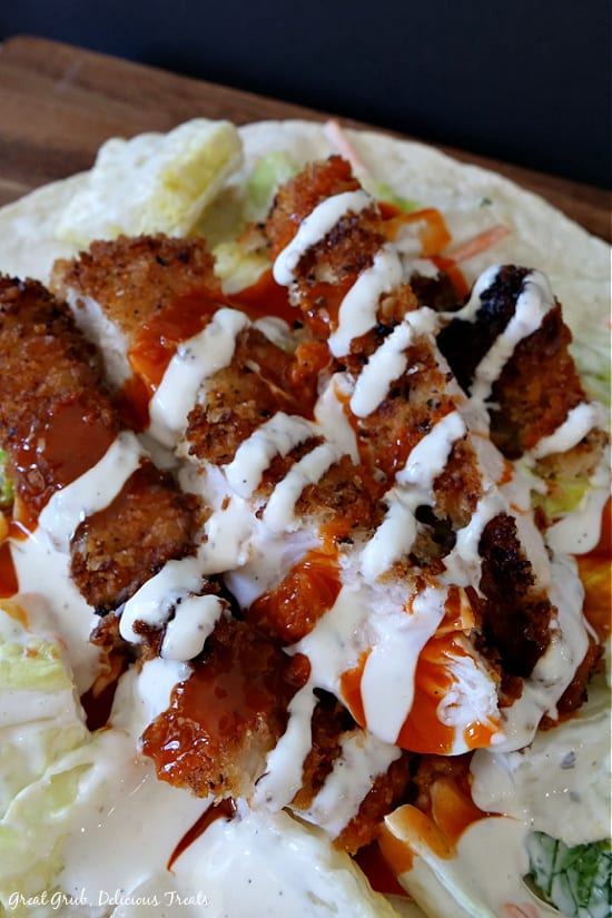 A close up photo of a flour tortilla topped with three pieces of crispy chicken strips with lettuce and then drizzled with ranch dressing and buffalo wing sauce.