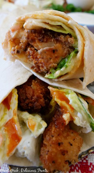 A super close up photo of two flour tortillas wrapped around crispy chicken breasts with lettuce, ranch and buffalo sauce showing out of the end of the tortillas.