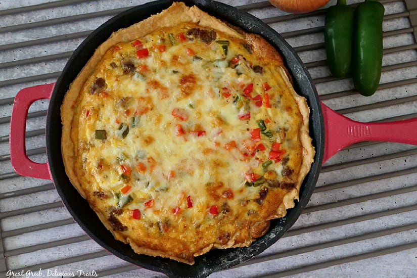 A red cast iron pan showing a baked Southwest Breakfast Quiche that is still in the pan.