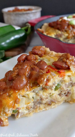 A slice of southwest breakfast quiche topped with chili, sitting on a white plate with a cast iron skillet, jalapenos, and a grey bowl full of chili in the background.