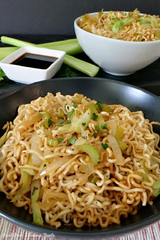 A black bowl and a white bowl filled with homemade chow mein with a little square bowl filled with soy sauce and two celery stalks in the background.
