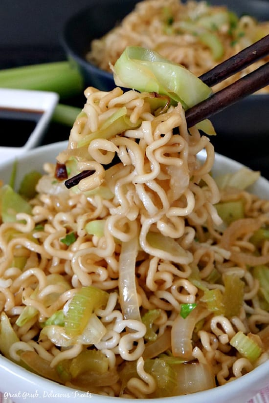 A close up photo of two chopsticks picking up a large amount of chow mein from a white bowl.