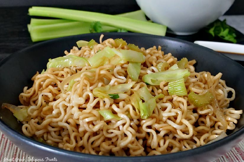 A black bowl filled with homemade chow mein with a white bowl and celery stalks in the background.