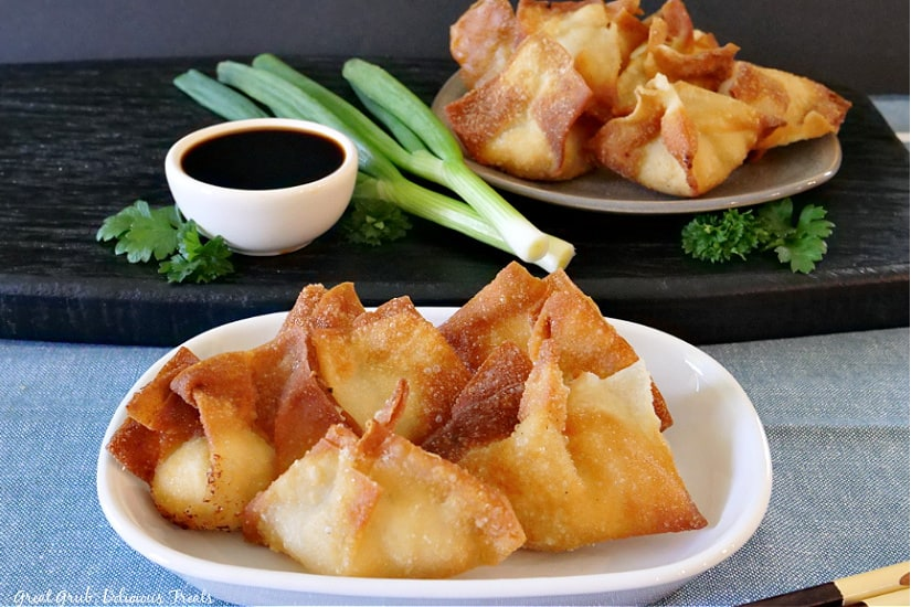 Two plates with 5 crispy fried cream cheese wontons place on them with a small white bowl of soy sauce, green onions and parsley on a black board.