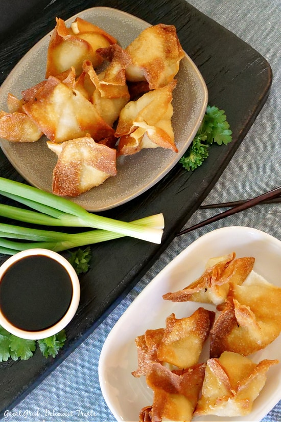 An overhead photo of two plates with a stack of crispy cream cheese wontons on them one on a blue placemat and the other on a black board along with a small white bowl of soy sauce and green onions with chopsticks off to the side.