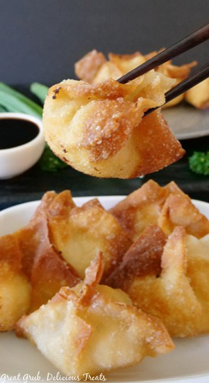 A single fried wonton being held with chopsticks above a white plate with more wontons on it.