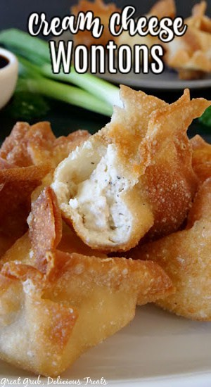 A close up photo of a wonton with a bite taken out of it place on top of more wontons.