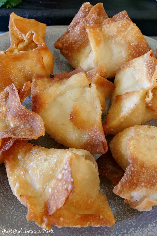 A close up photo of a light grey plate with 7 cream cheese wontons on it.