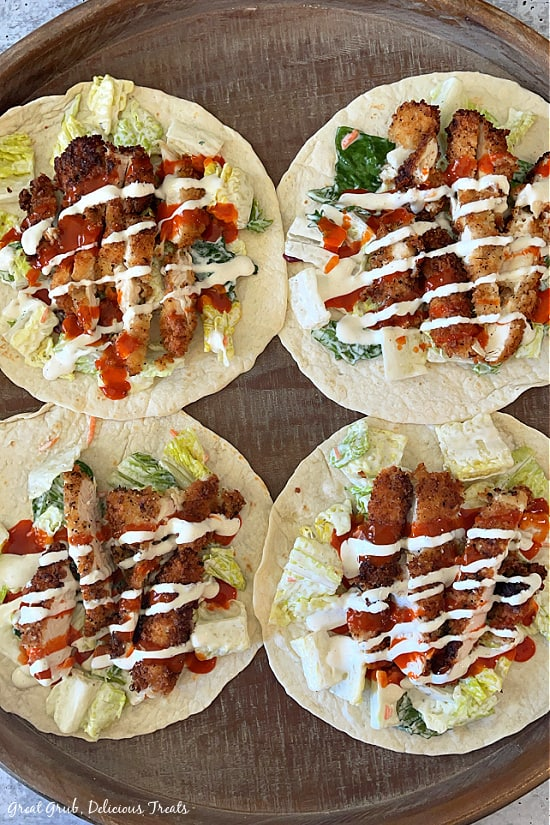 Four flour tortillas with crispy chicken strips on each tortilla with lettuce, ranch dressing and buffalo wing sauce drizzled over the top and all four placed on a round wooden carrying tray.
