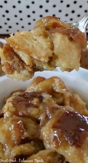 A spoonful of caramel bread pudding held up over a white bowl filled with caramel bread pudding.