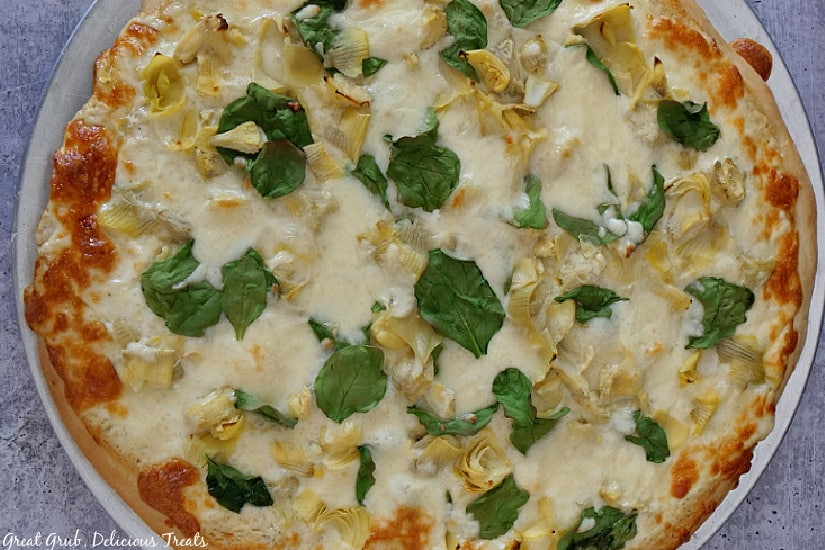 A whole Spinach Artichoke Alfredo Pizza on a pizza baking sheet placed on a grey table.