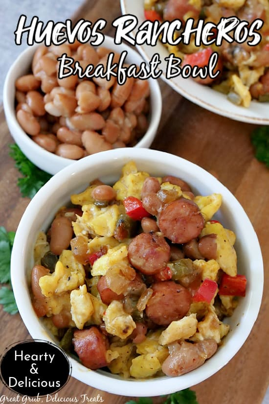 A white bowl on a brown cutting board, loaded with eggs, sausage, beans, and bell peppers.
