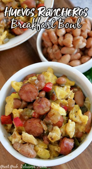 A white bowl filled with pinto beans, eggs, bell peppers, onions, and sausage.