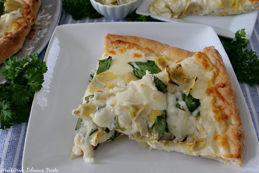 A white plate with two slices of spinach artichoke alfredo pizza on it.