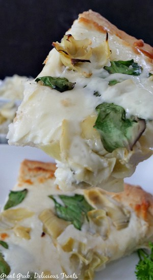 A close up photo of 2 slices of spinach artichoke alfredo pizza on a white plate.