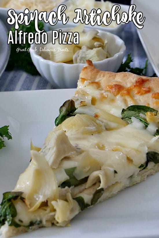 A slice of spinach artichoke alfredo pizza on a white plate with a small white bowl filled with artichokes in the background.