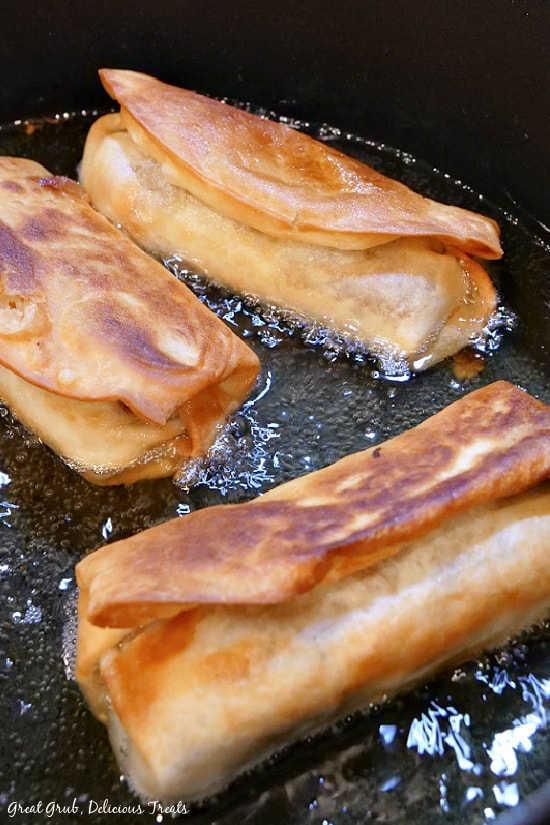 Three fried burritos being fried in oil.