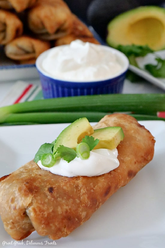 A white plate with a fried burrito with sour cream, sliced avocado, green onions and cilantro on top.