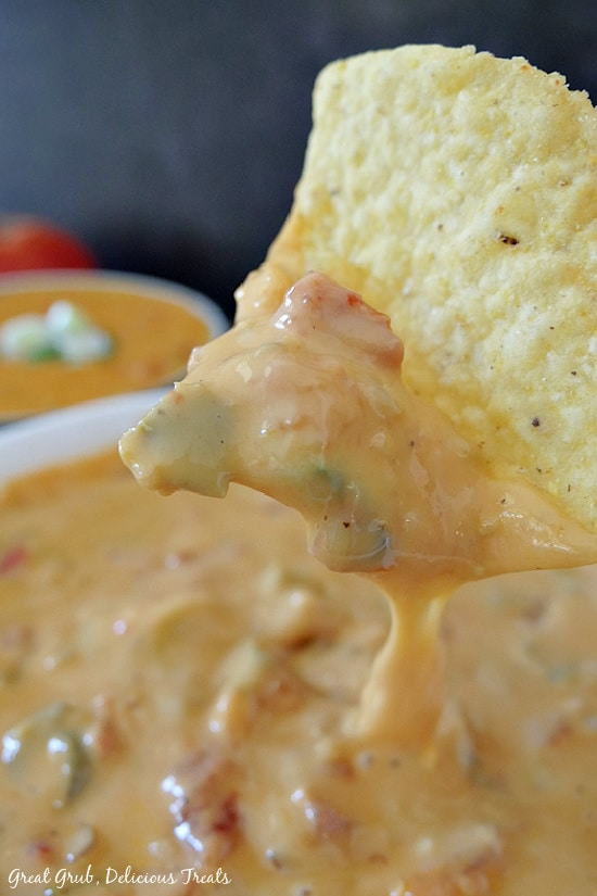 A white bowl filled with spicy queso and a close up shot of a tortilla chip that has been dipped into the queso.