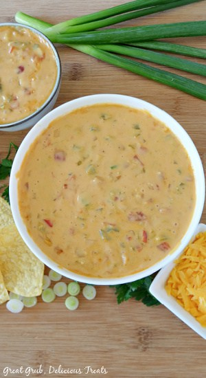 A white bowl sitting on a wood cutting board filled with spicy queso.