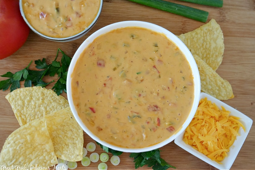 Two white bowls filled with spicy queso sitting on a wood cutting board with tortilla chips, shredded cheese, cilantro and sliced green onions along side of the bowls.