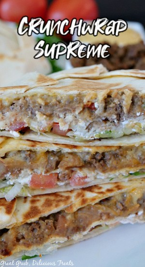 A picture of Crunchwrap Supremes cut in half and stacked on top of each other on a white plate with tomatoes, cooked ground beef, and tortillas in the background with the title at the top center.