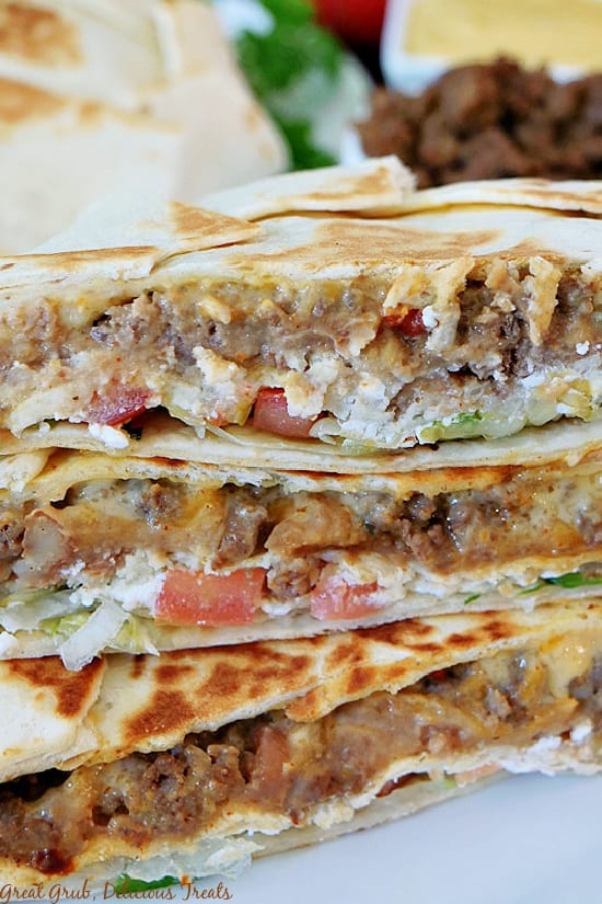 A close up picture of halved Crunchwrap Supremes stacked on top of each other with taco meat, nacho cheese, and parsley in the background.